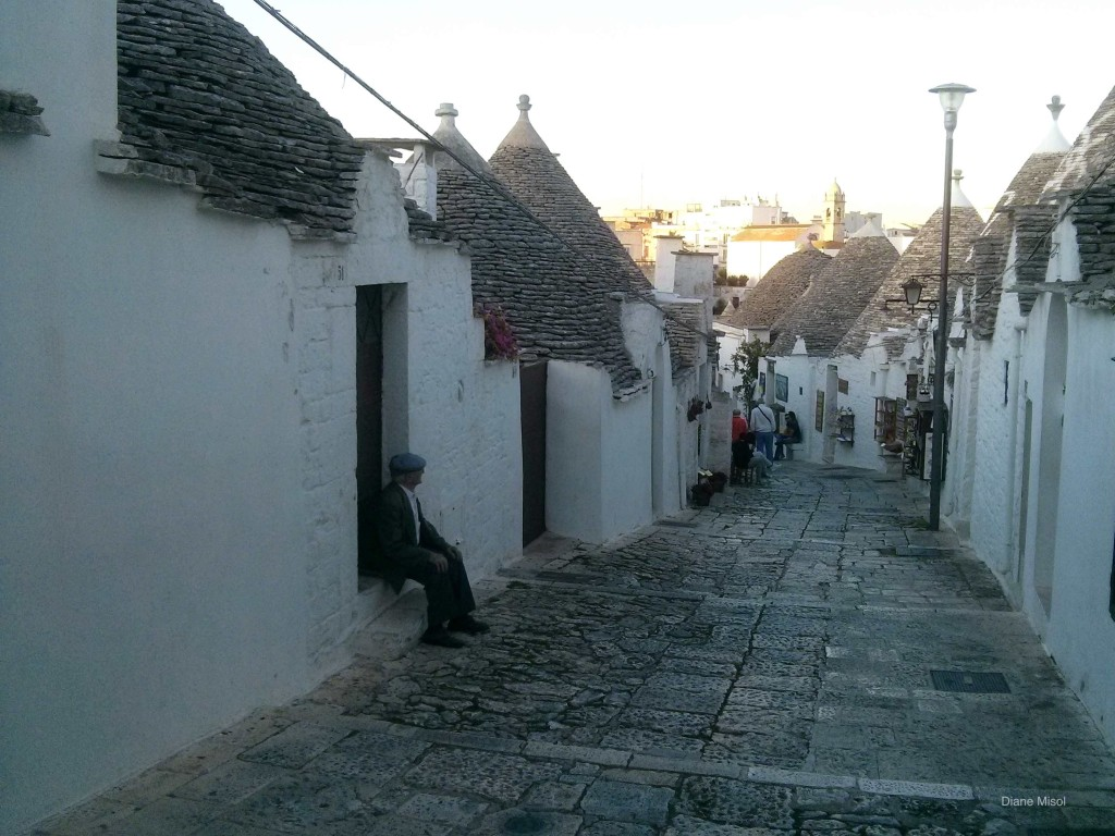 Man sits in doorway, Puglia, Italy, Trulli