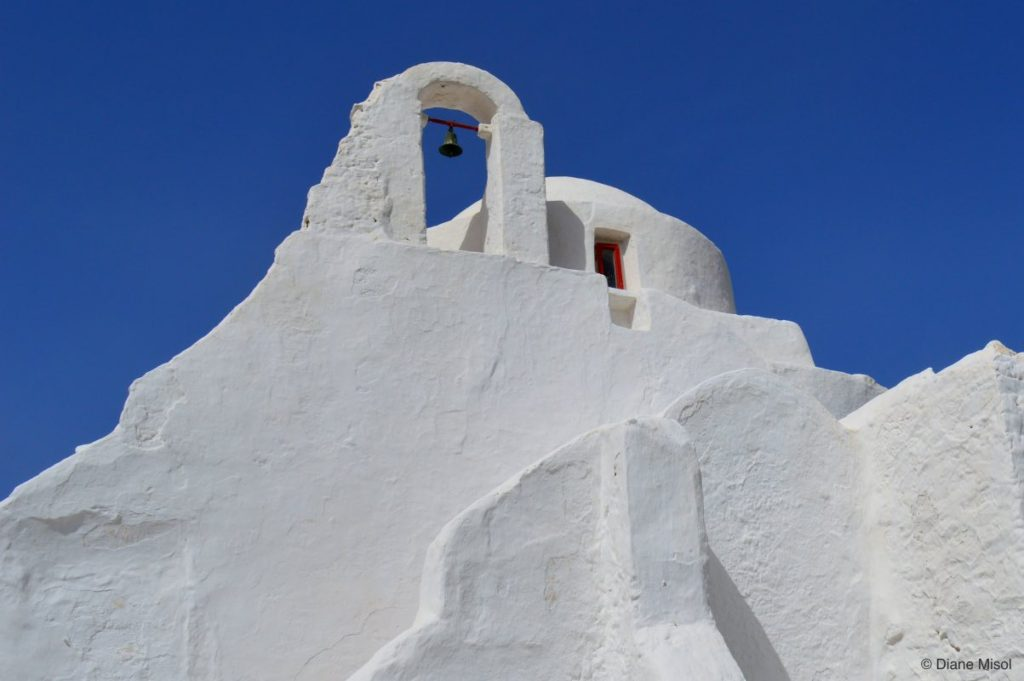 Single Bell Tower and a Little Red Door. Mykonos, Greece