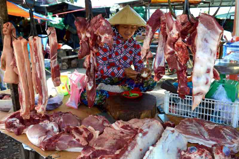 Meat Vendor Sits on her Stand Eating an Egg - Phu Quoc, Vietnam