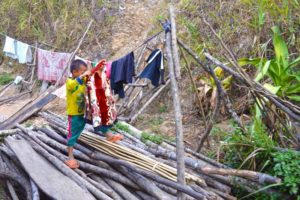 Child Hanging Washed Clothes - Laos
