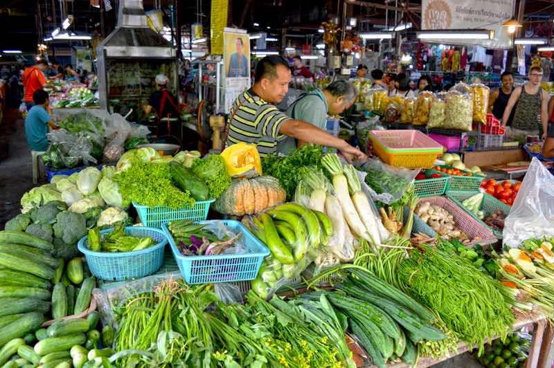 City Market Veggies - Cooking School Participants smile in background - Chiang Mai, Thailand